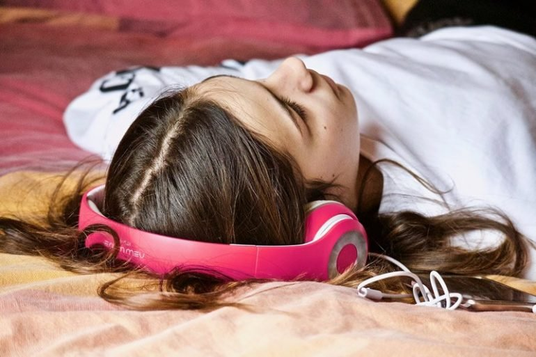 This shows a girl listening to music on headphones