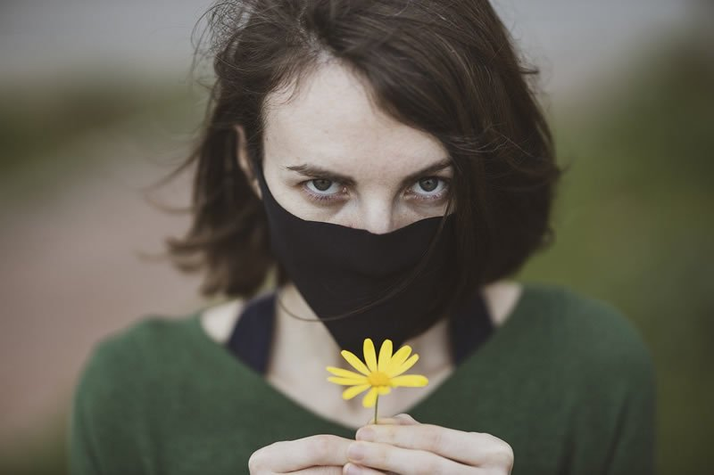 This shows a woman in a facemask holing a flower