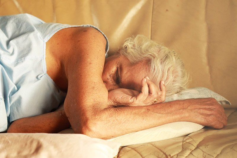 This shows an older woman sleeping