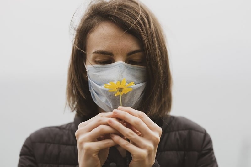 This shows a woman in a facemask smelling a flower