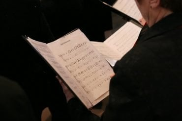 This shows a person singing in a choir