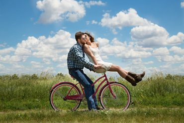 This shows a couple on a bicycle
