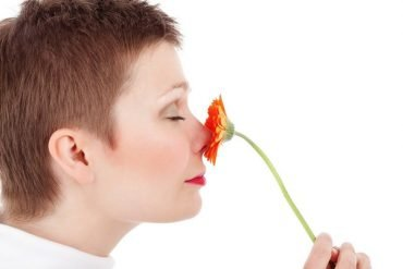 This shows a woman smelling a flower