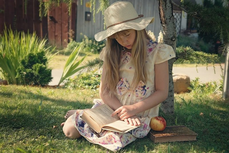 This shows a little girl reading a book