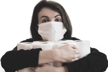 This shows a woman in a face mask hugging rolls of toilet paper