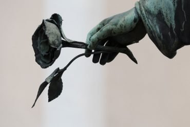 This shows a statue of a hand holding a rose