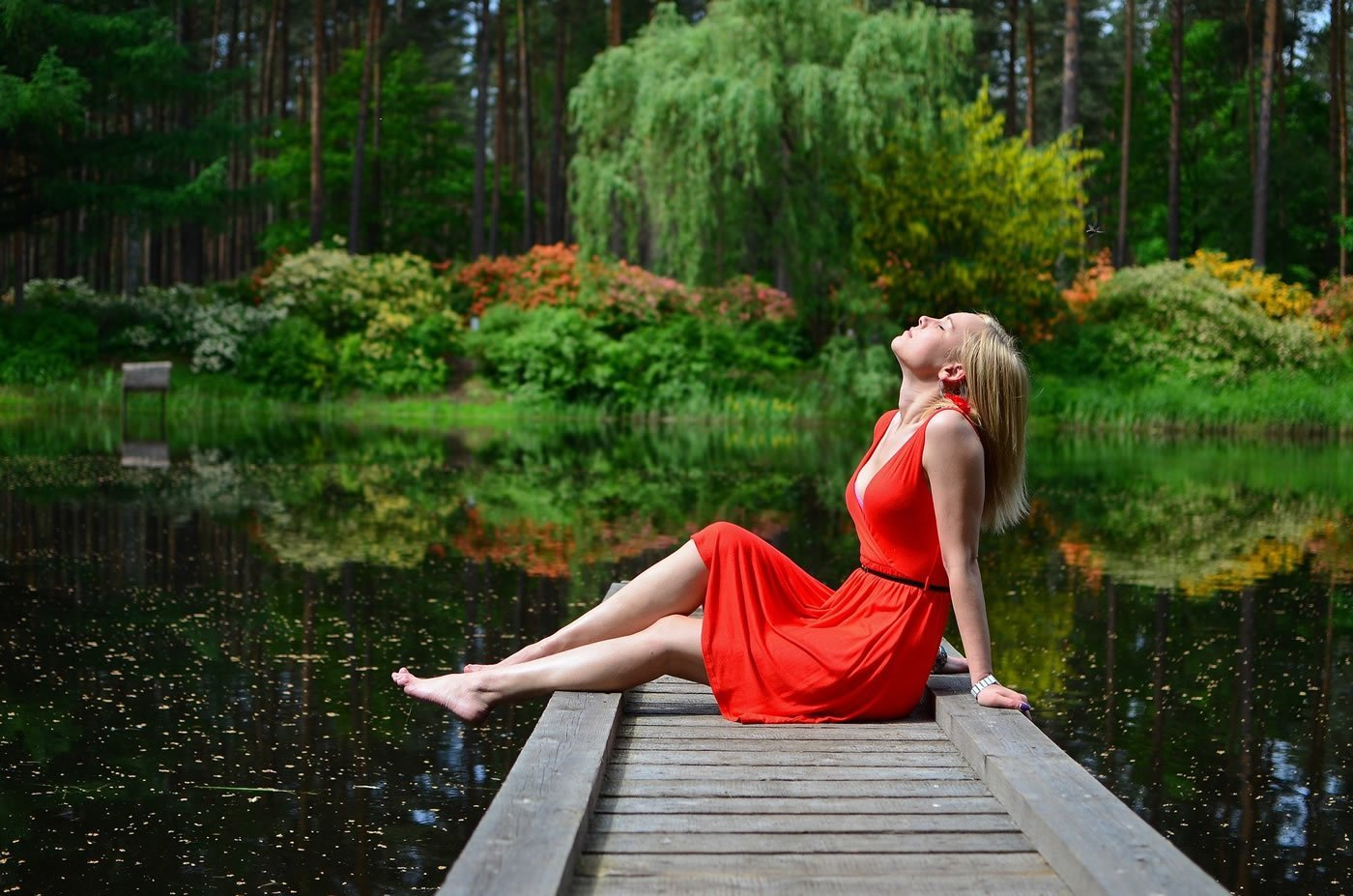 This shows a woman relaxing by a lake
