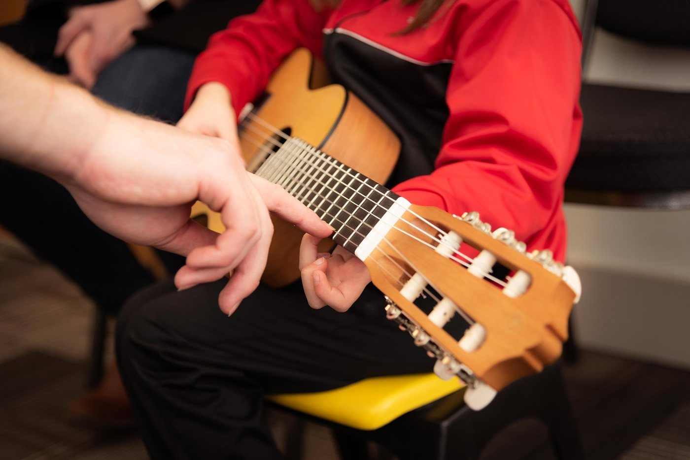 This shows a child learning guitar