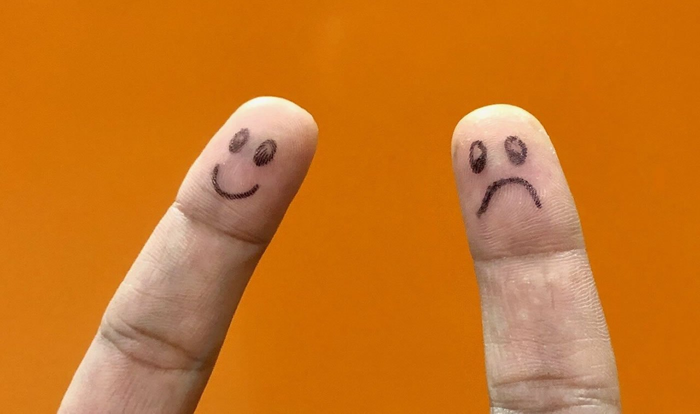 This shows two fingers, one has a smiley face drawn on it, the other has a frowning face