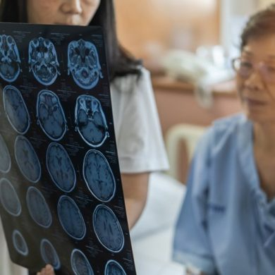 This shows a doctor looking at brain scans