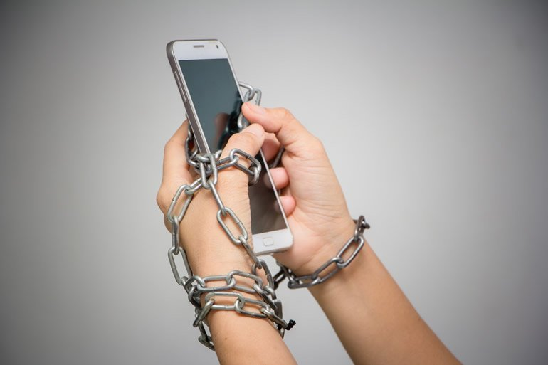 This shows a person's hands chained to a cell phone
