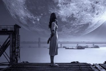 This shows a woman standing on a dark beach