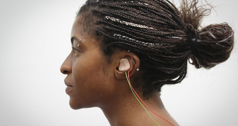 This shows a woman with the tVNS device in her ear