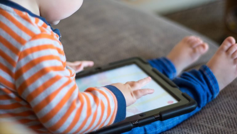 This shows a toddler with a tablet