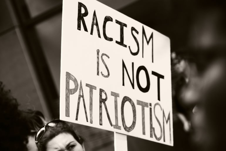 This shows a person holding a sign that reads racism is not patriotism