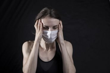 This shows a stressed woman in a facemask