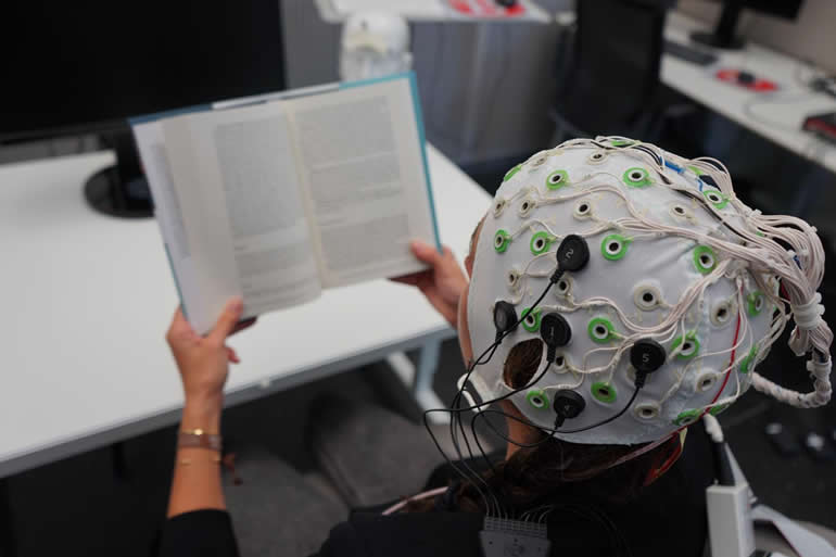 This shows someone in an eeg cap reading a book