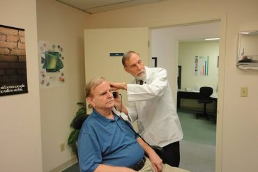 This shows a man getting a hearing test