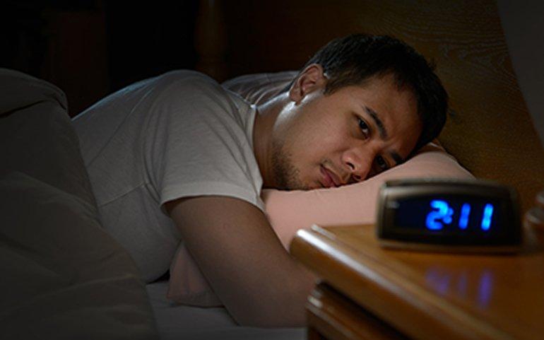 This shows a man laying awake