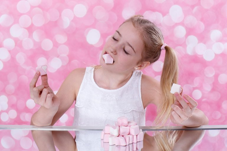 This shows a girl eating a marshmallow