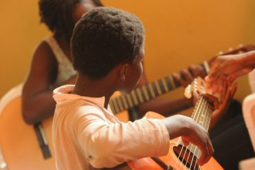 This shows two children playing guitars