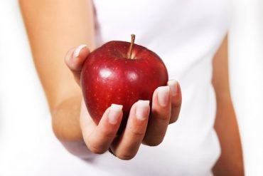 This shows a woman holding an apple