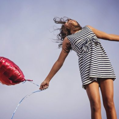 This shows a happy woman with a heart balloon