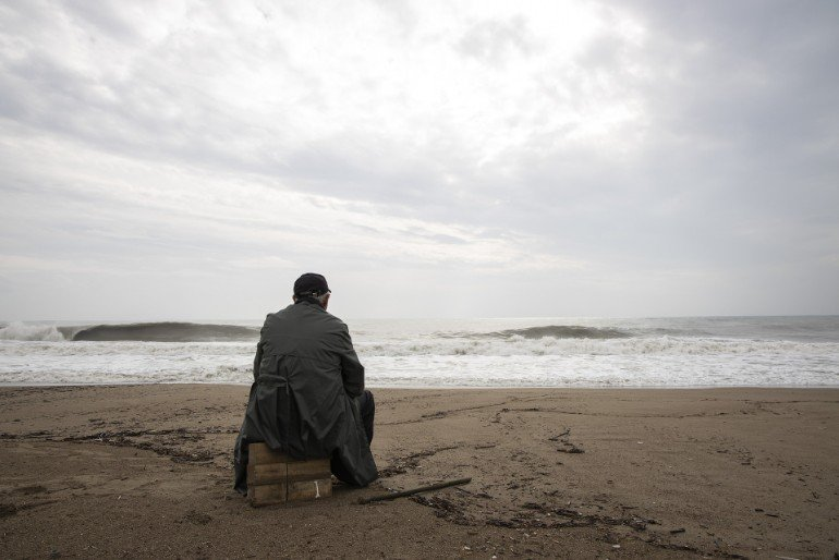 This shows a man sitting alone on a beach