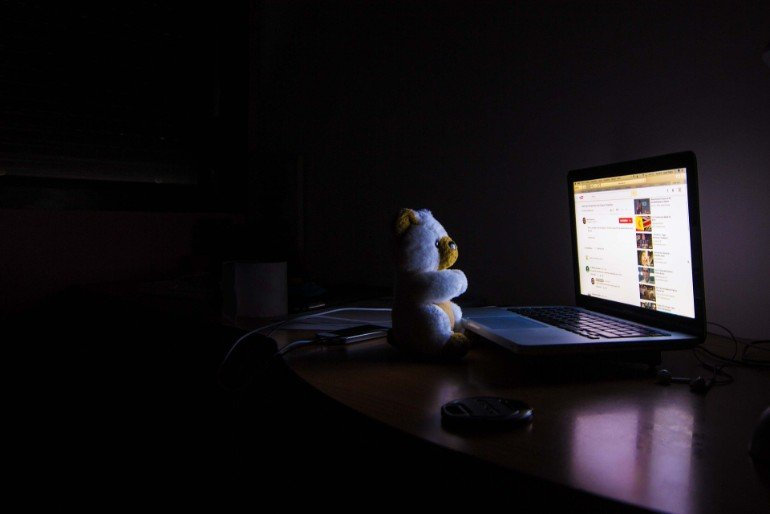 This shows a teddybear sitting at a computer at night