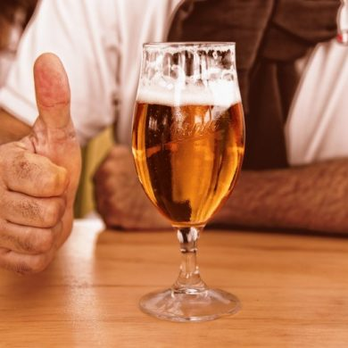 This shows a glass of beer and a man's thumb