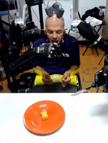 This shows the patient using the robotic arms to feed himself
