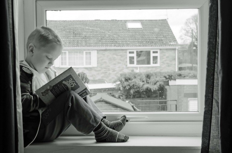 This shows a child reading at a window
