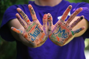 This shows words written in bright colors on a woman's hands