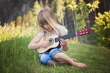 This shows a little girl playing a guitar