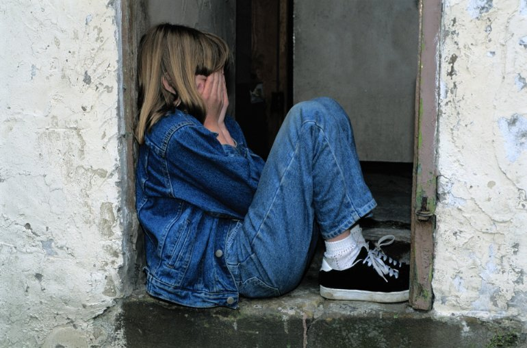 This shows a young girl crying and alone in a doorway