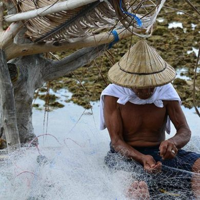 This shows a man fixing a fishing net