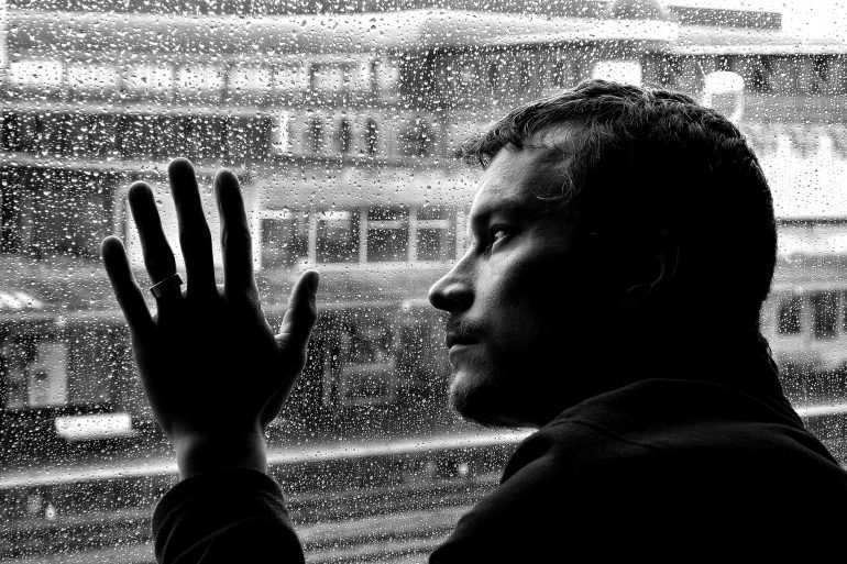 This shows a depressed looking man looking at the rain from a window