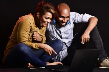 The image shows two young adults laughing while looking at a computer monitor