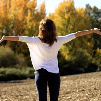 This shows a woman with her arms outstretched in a beautiful field