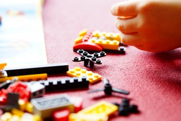The image shows a child playing with lego blocks