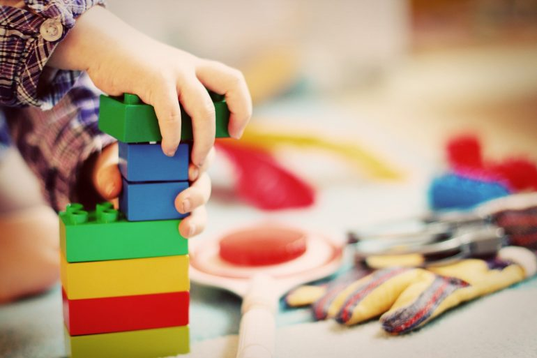 This shows a child playing with colorful building blocks