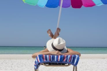 This shows a woman sunbathing on a beach