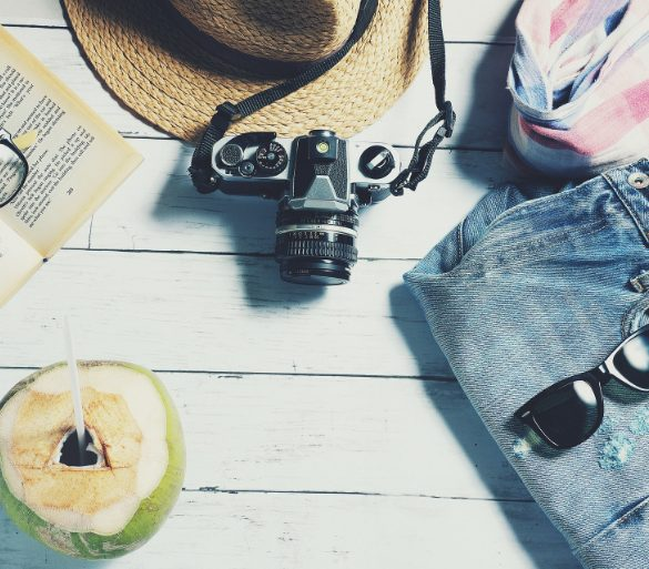 This shows a straw hat, camera and other travel related apparel