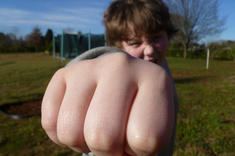 This shows a little boy with his fist out like he is punching