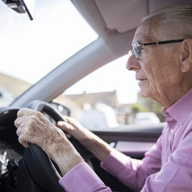 This shows an older gentleman driving a car