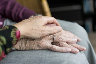 This shows someone holding an older lady's hands