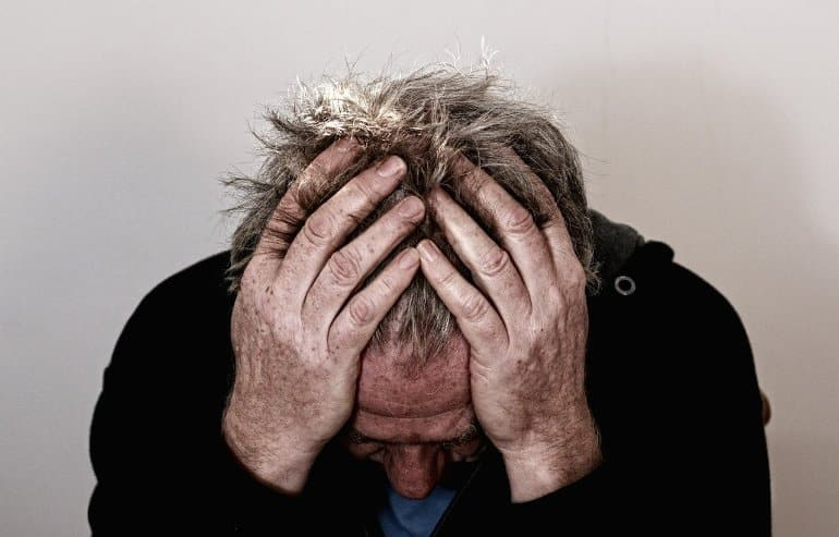 This shows an older man holding his head in pain