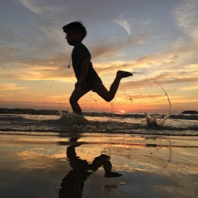 This shows a young boy running on a beach