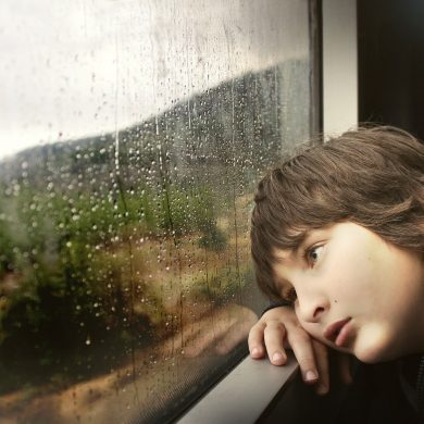 This shows a little boy looking out of a window
