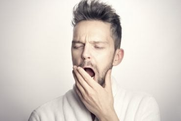 This shows a bored looking man yawning